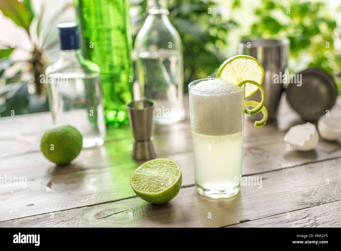 Egg Gin Fizz Cocktail with Lime Garnish. Making Gin Fizz Drink with ingredients. - Stock Image