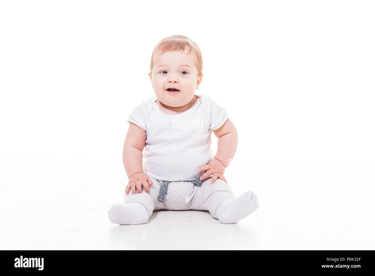 smiling baby sitting on a floor - Stock Image