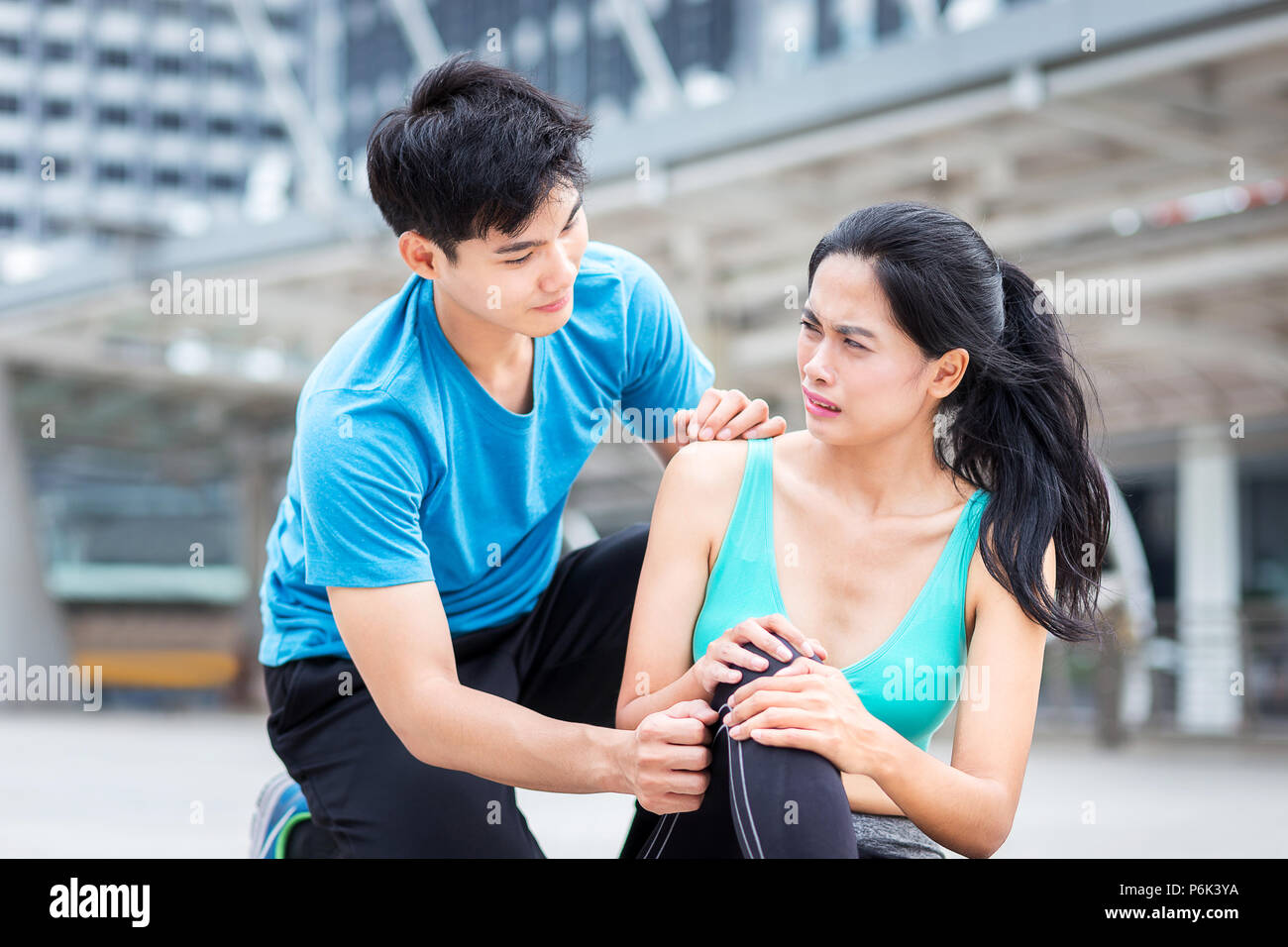 running injury, man help sport girl from  ankle hurt accident from playing sport in the city - Stock Image