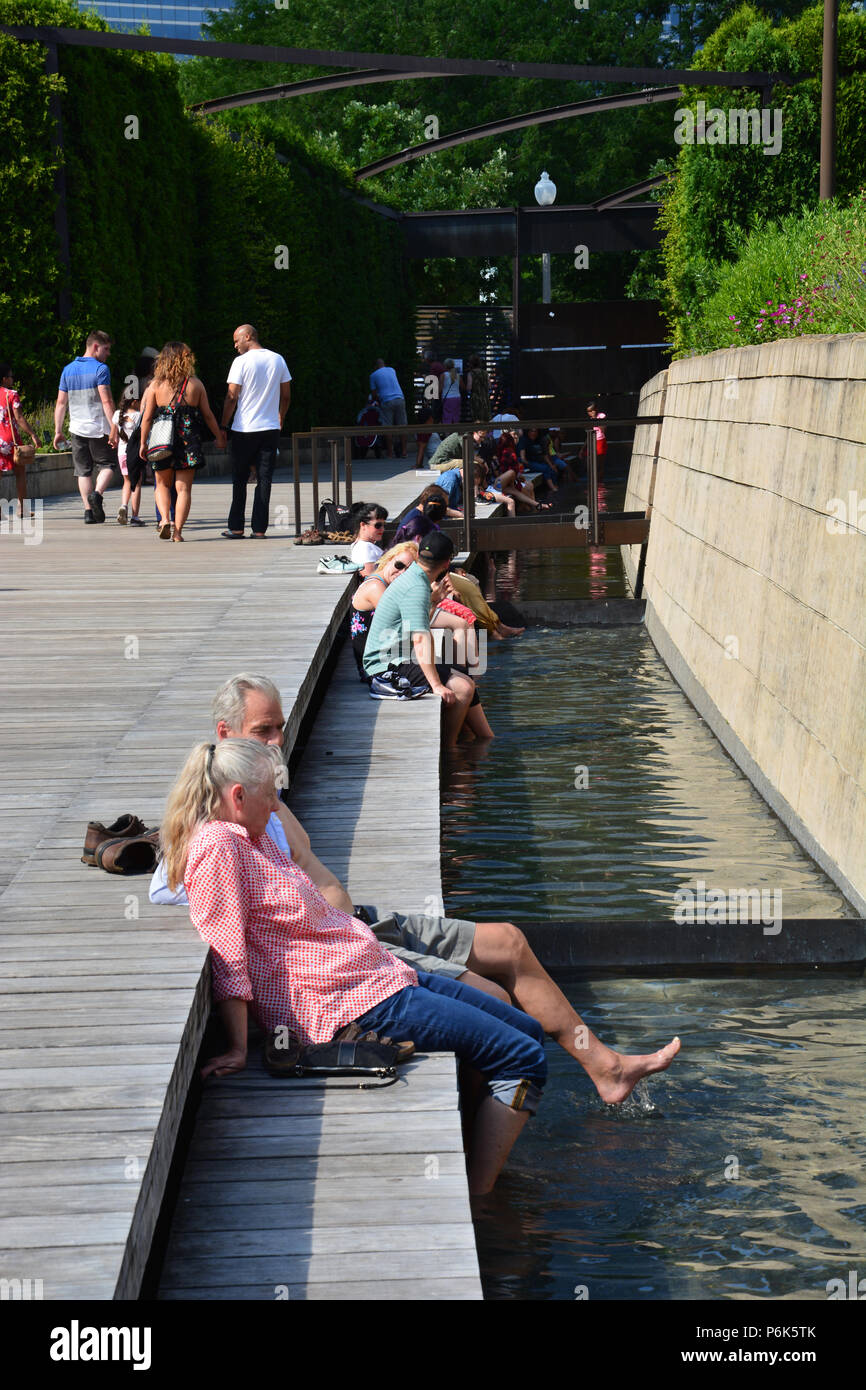 A couple cools off on a hot summer afternoon in the Lurie Garden river at Chicago's Millennium Park. - Stock Image