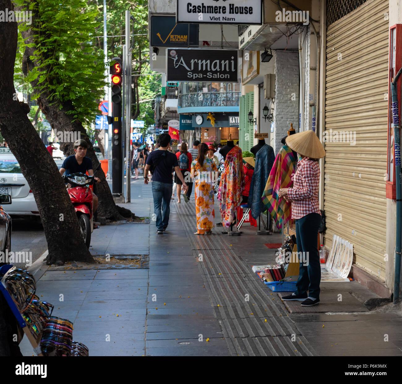 Saigon, Vietnam--March 19, 2016.  A  busy luxury shopping street in Saigon; a street merchant displays merchandise for sale. - Stock Image