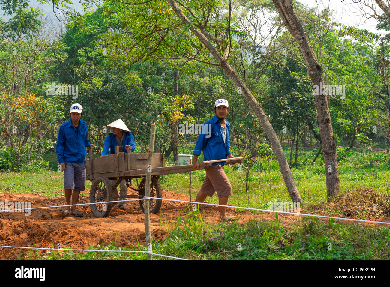 Chan May,  MySon, Vietnam -- March 22, 2016. Vietnamese workers toil in the gardens  of  My Son, in Vietnam. Stock Photo
