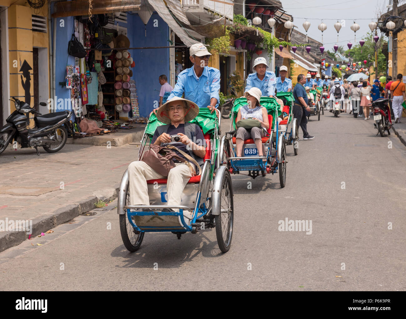 Hoi An, Vietnam--March 23, 2016. Tourists explore the city Hoi An on the while riding pedicabs on a busy shopping street. - Stock Image