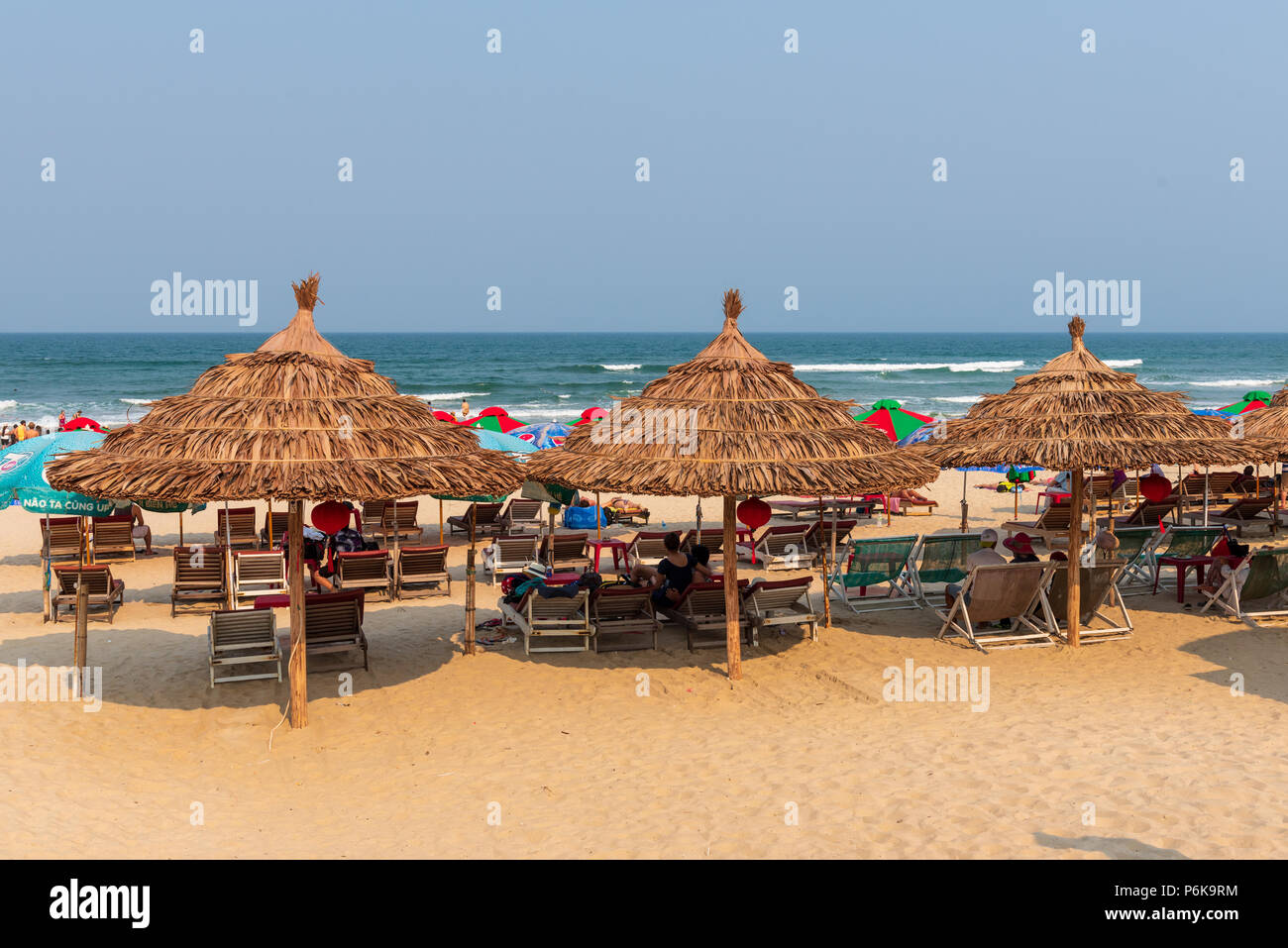 Da Nang, Vietnam--March 23, 2016. Sun bathers relax on lounge chairs under thatched roof umbrellas on China Beach. - Stock Image