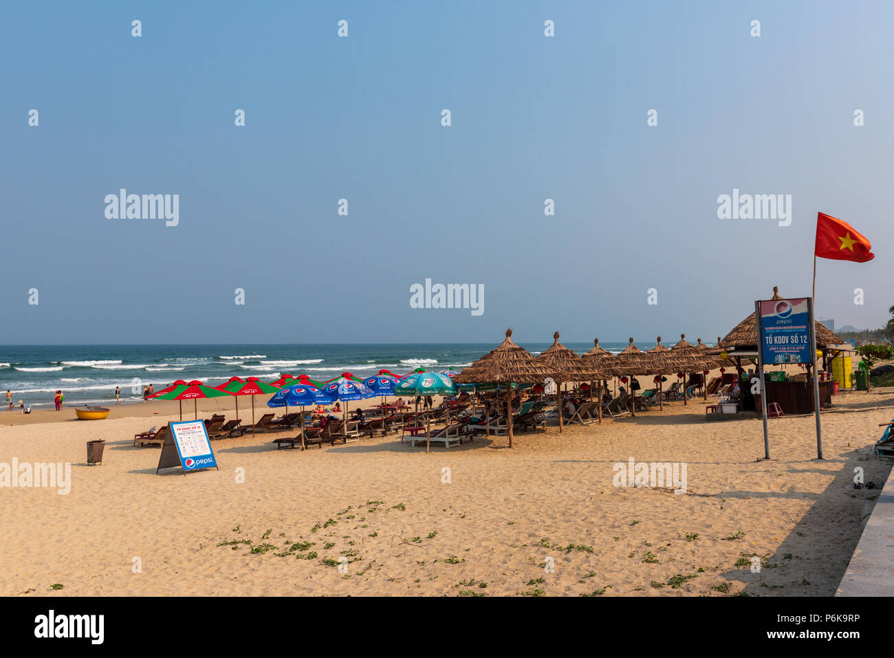 Da Nang, Vietnam--March 23, 2016. Sun bathers relax on lounge chairs and swim in the South China Sea at the popular China Beach. - Stock Image