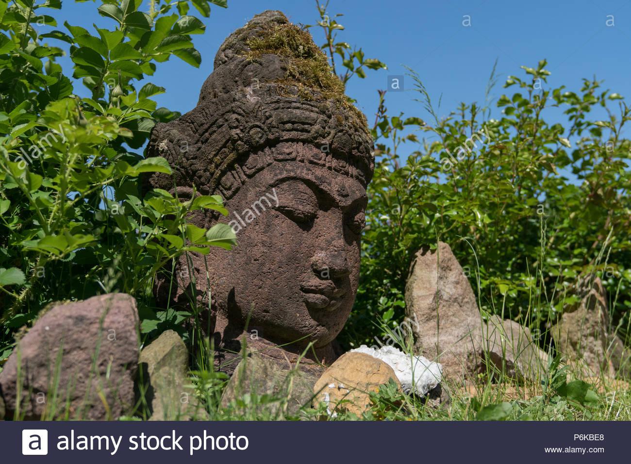 Closeup of an Indian buddhism stone sculpture in a green garden - Stock Image
