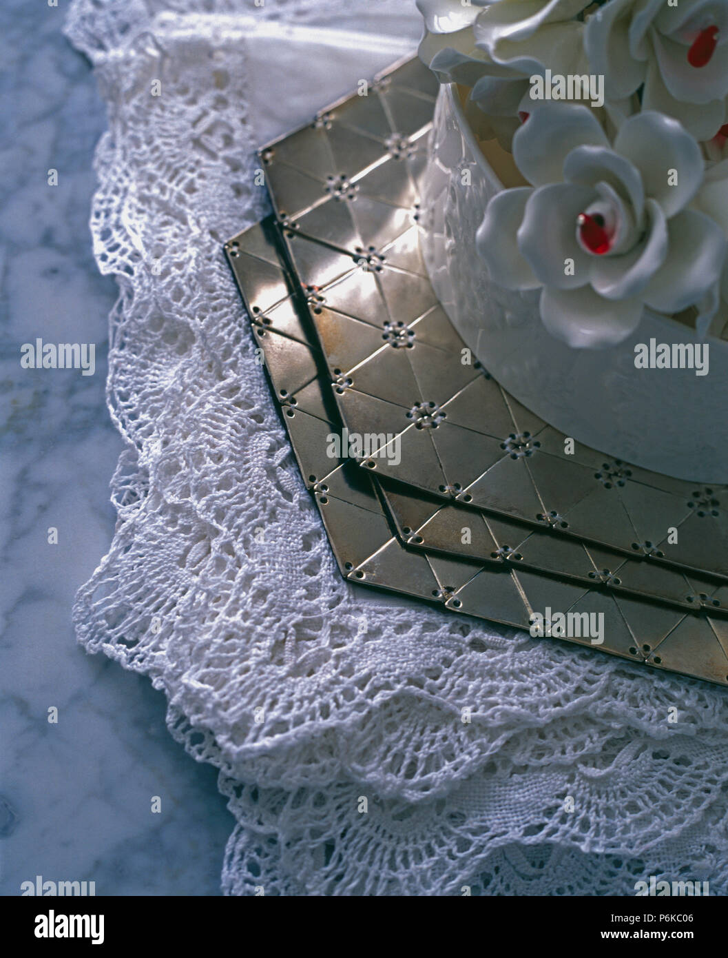 Close-up of hexagonal metal placemats on folded lace tablecloths Stock Photo