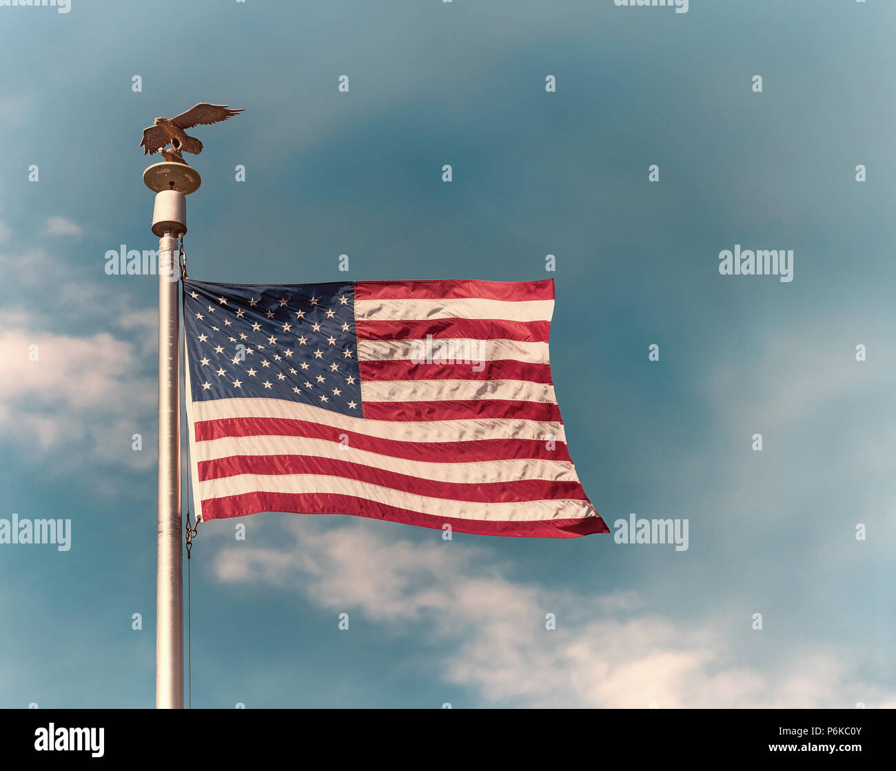 American flag on pole waving in the wind against blue sky and white clouds background. Vintage toned. - Stock Image
