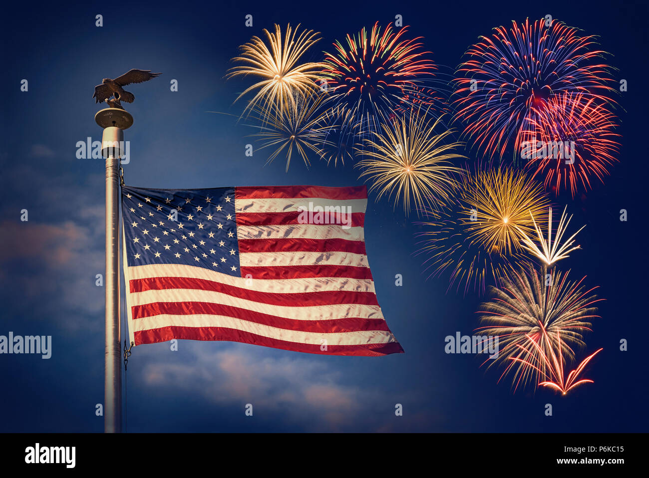 Festive fireworks display with American flag waving against the dark blue night sky. Concept for 4th of July celebration. - Stock Image