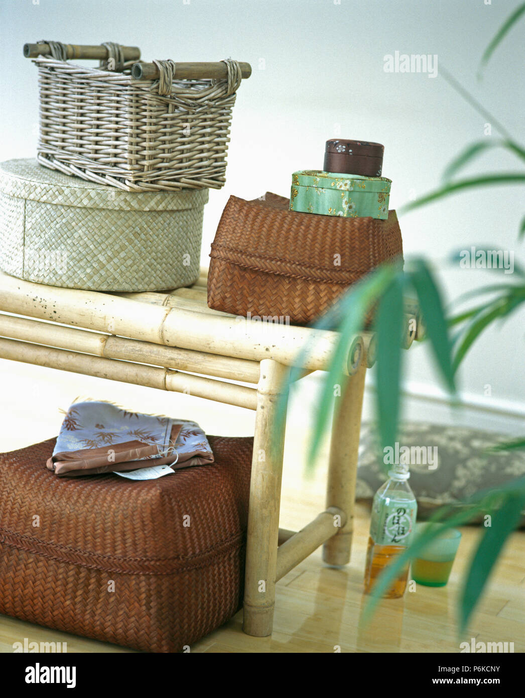 Close Up Of Lidded Wicker Storage Boxes On Bamboo Stool