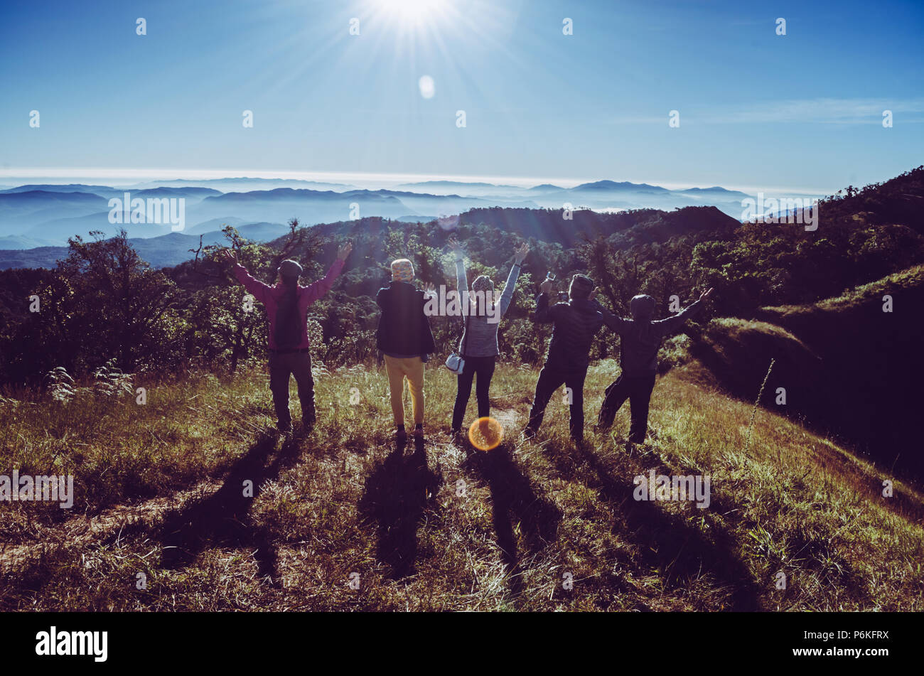 Group of Traveler on mountain summit enjoying aerial view hands raised over clouds Travel Lifestyle success concept adventure active vacations outdoor Stock Photo