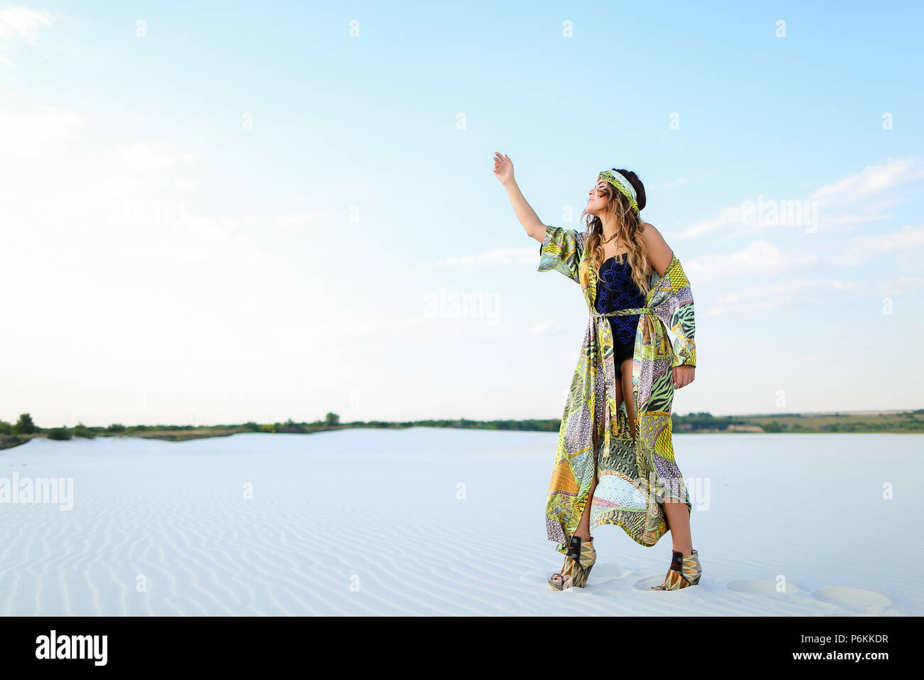 Caucasian stylish female photo model with raised hand wearing bl - Stock Image