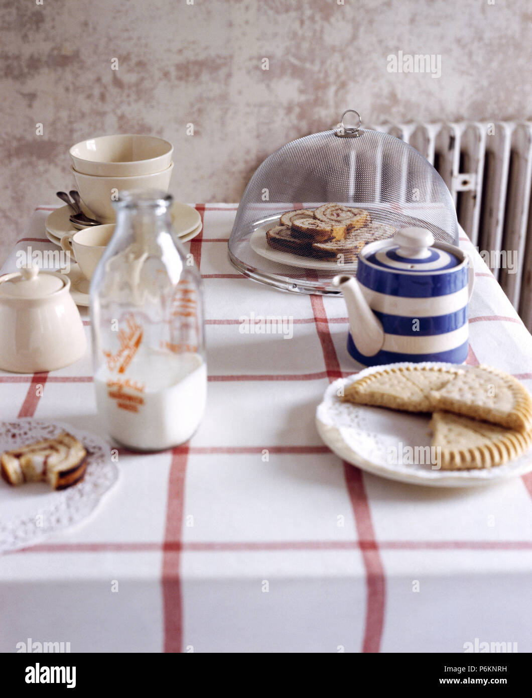 Blue+white striped teapot and a vintage glass milk bottle on a table with a checked cloth and a plate of shortbread - Stock Image