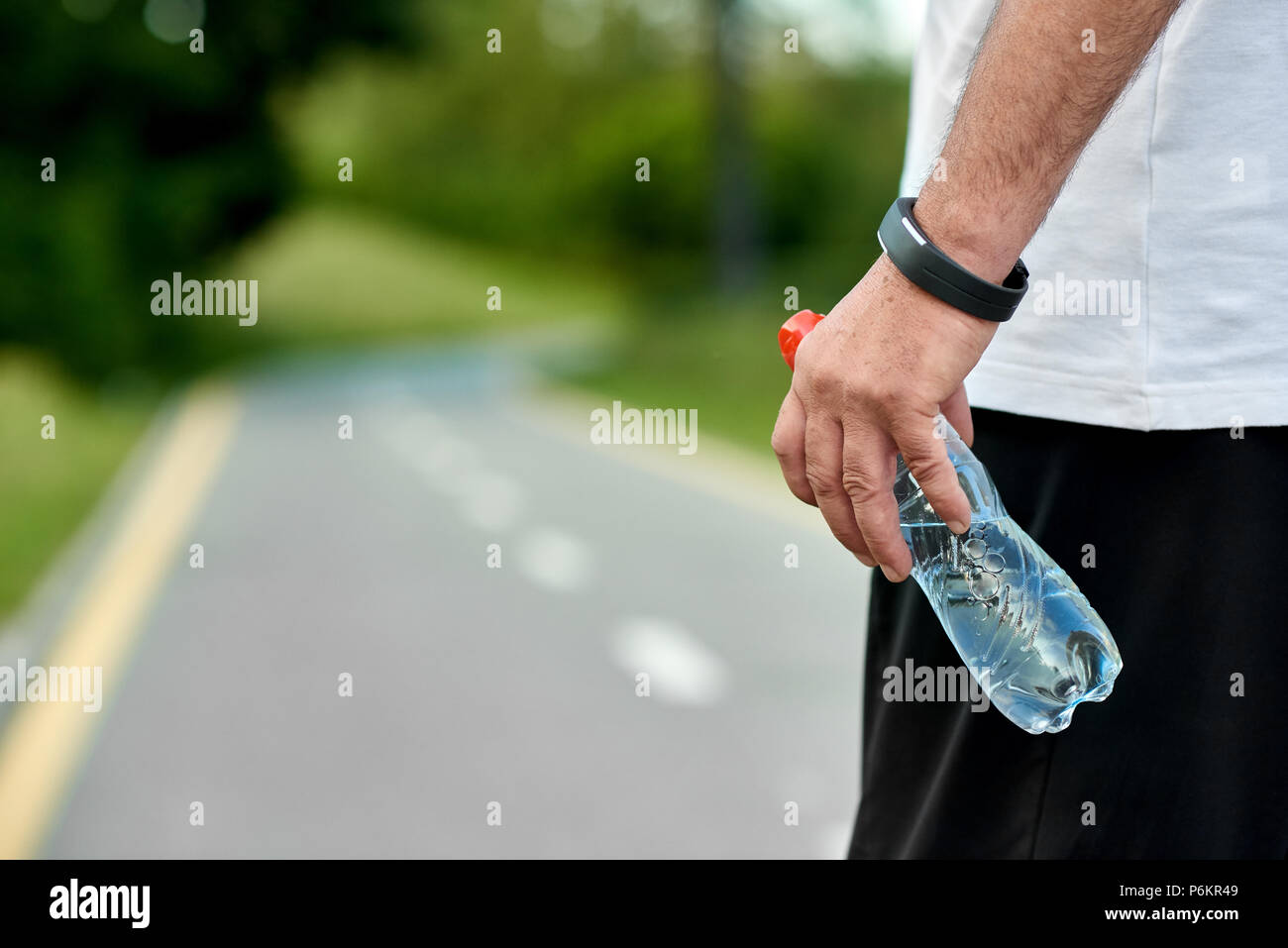 Sportsman's hand keeping water bottle runningon racetrack. Keeping body fit, muscular, strong. Maintaining healthy lifestyle. Wearing white t-shirt, black trosers, sport handwatch. Ready to run. - Stock Image