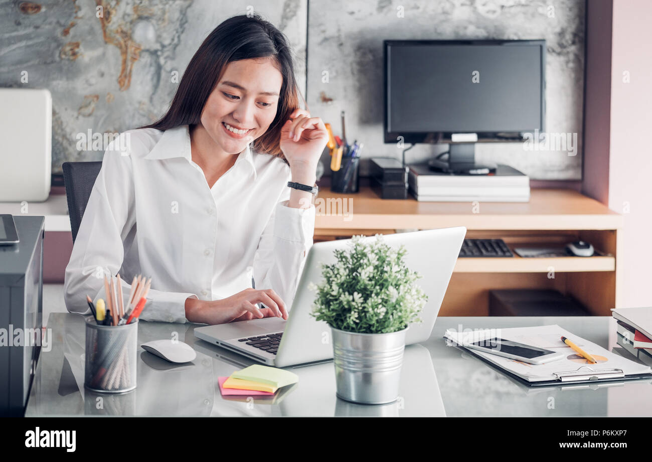 Asia businesswoman looking at laptop computer and smiling face and rest chin on hand with happy emotion from good news of business success in home off - Stock Image