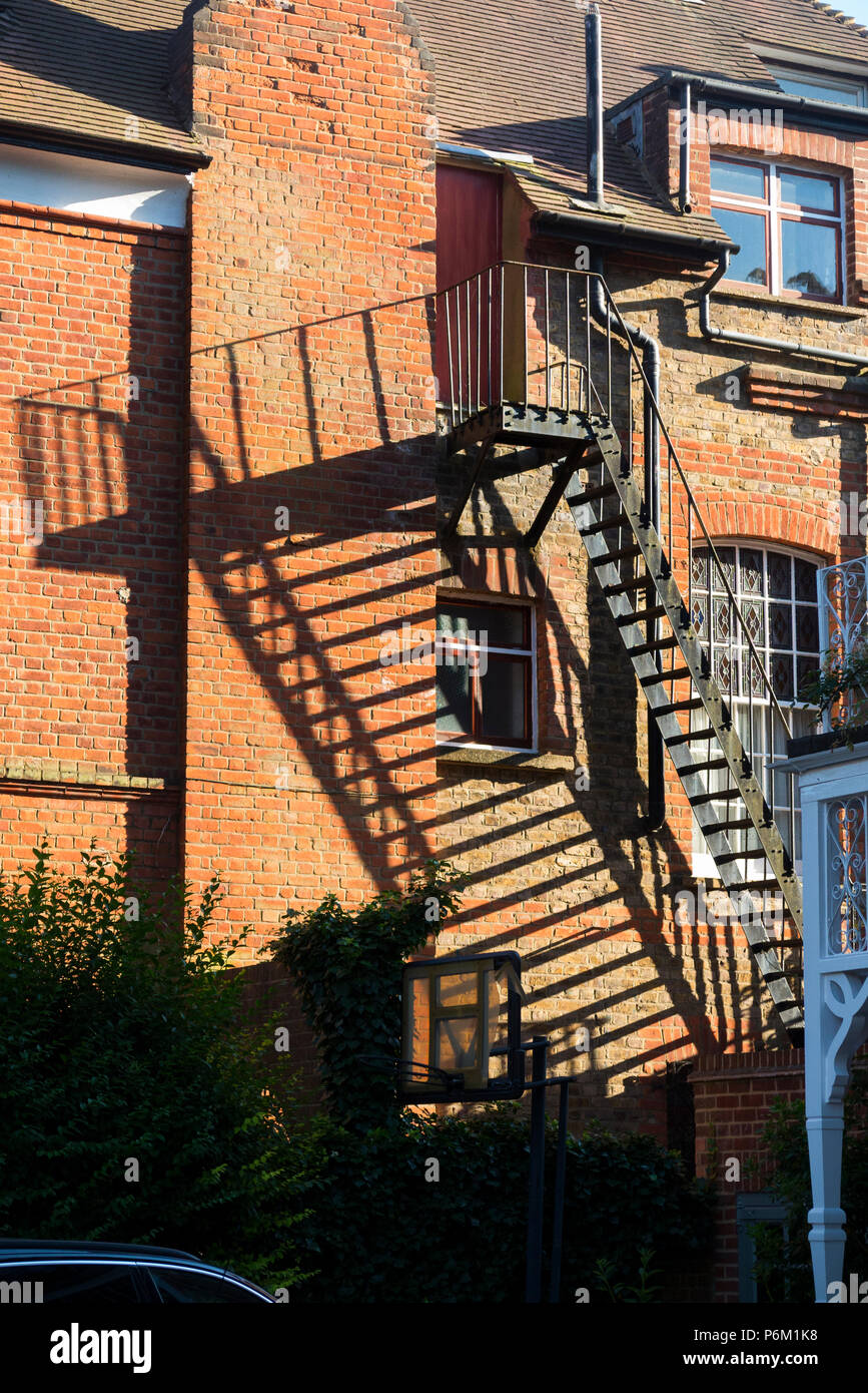 Side escape staircase made of metal, probably iron, which could be used as a fire escape or emergency exit: fitted to the side of a Victorian home house building in London. (99) - Stock Image