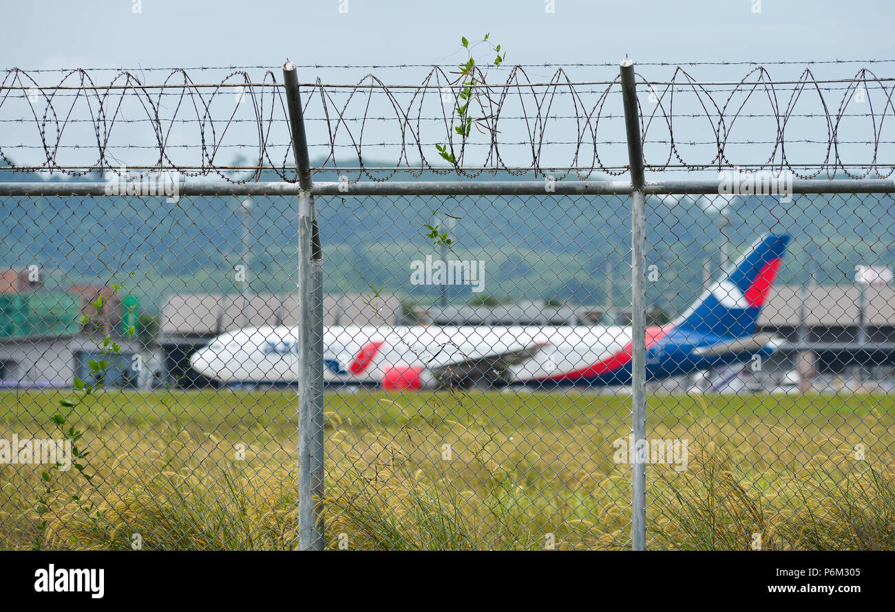 Phuket, Thailand - Apr 23, 2018. Fence with barbed wire around airport with a docking airplane in Phuket International Airport (HKT). Stock Photo