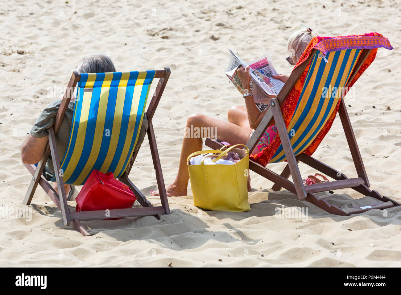 Bournemouth, Dorset, UK. 1st July 2018. UK weather: hazy sunshine, but still warm as thousands of sunseekers head to the beaches at Bournemouth to enjoy a day at the seaside. Couple relaxing in deckchairs on beach, reading newspaper. Credit: Carolyn Jenkins/Alamy Live News - Stock Image