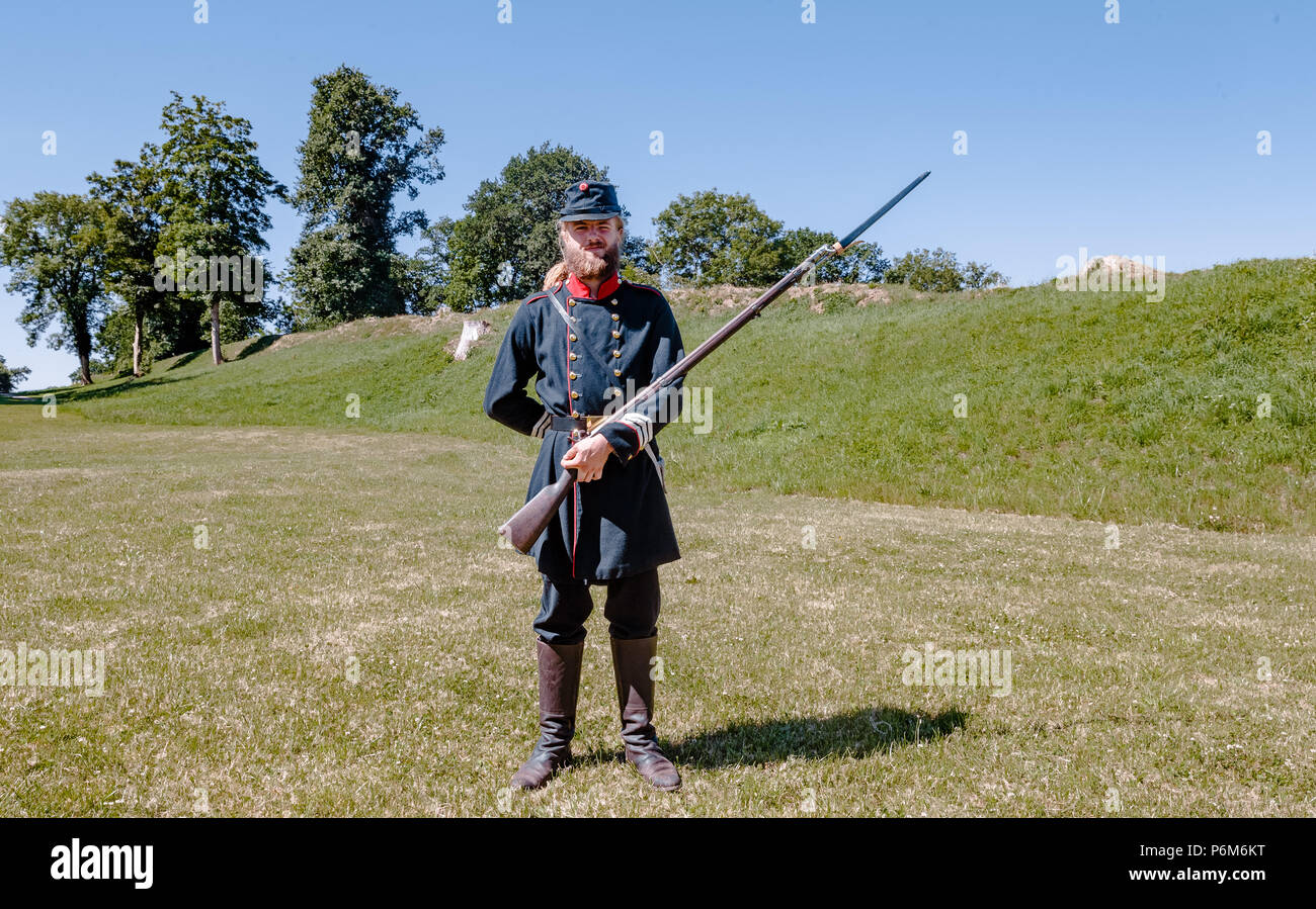 Danewerk, Germany. 01st July, 2018. An employee of the Danevirke Museum is dressed in a historic Danish military uniform, standing at the medieval Danish fortification site Danevirke. Danevirke, along with the viking settlement of Haitabu, was declared a UNESCO world cultural heritage on 30 June 2018. Credit: Markus Scholz/dpa/Alamy Live News - Stock Image