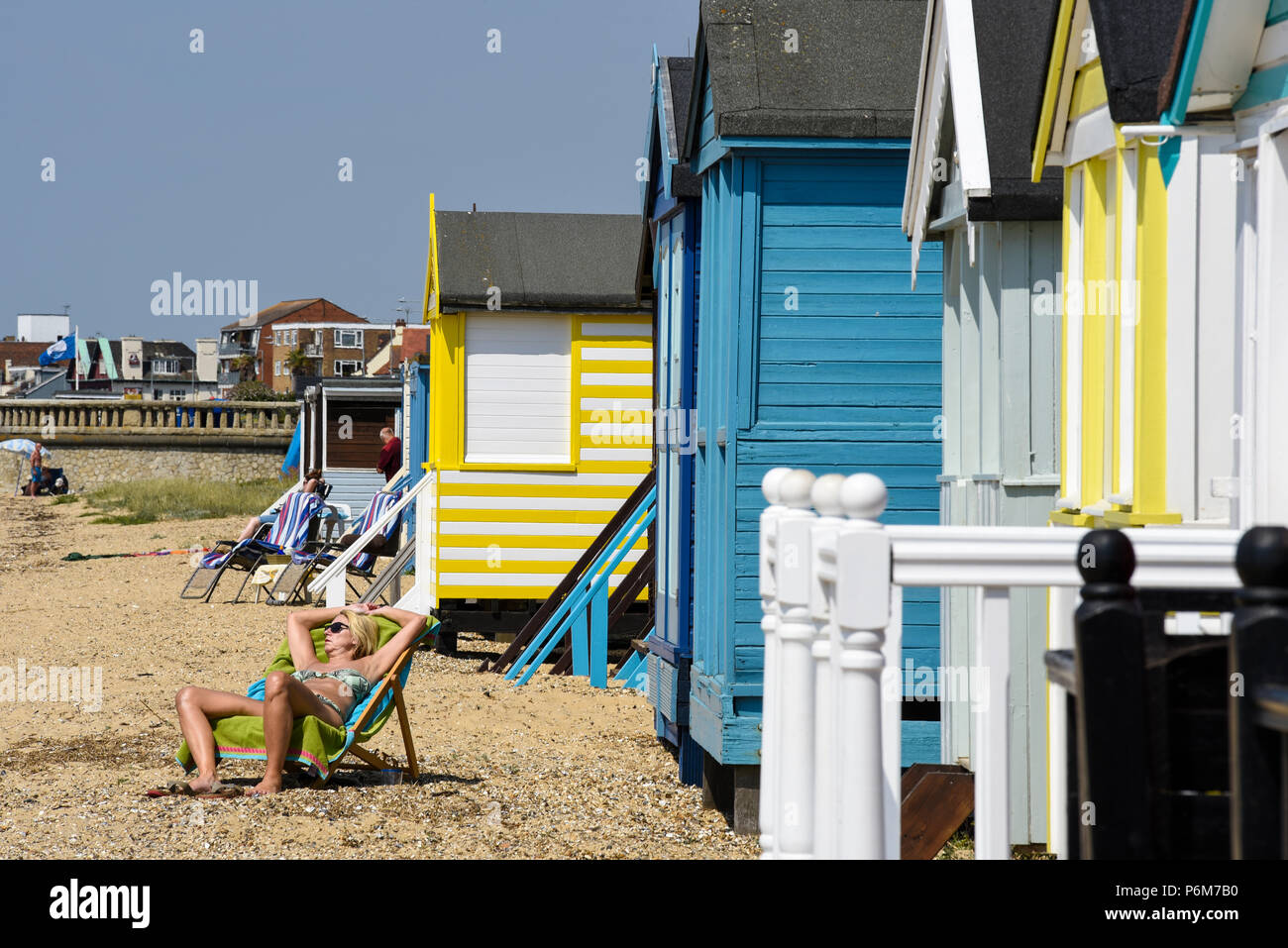Female sunbather by multi coloured brightly colored beach huts at Southend on Sea, Essex, UK - Stock Image