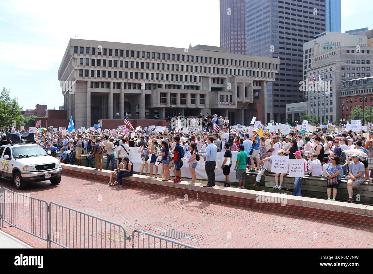 Boston, Massachusetts, USA. 30th June, 2018. IMMIGRATION BOSTON Citizens rally and march against separation of immigrant and migrant families and their children by the government and for the closing of the ICE, the Immigration & Customs Enforcement agency and against President Trump's immigration policies.Approximately 15,000 participants rallied on City Hall Plaza and marched to Boston Common Where more speeches were delivered. Notable speakers were Sen. Elizabeth Warren, Sen. Edward Markey, and Congressman Joe Kennedy III.Along the way a small group of 4 or 5 masked individuals, consid Stock Photo