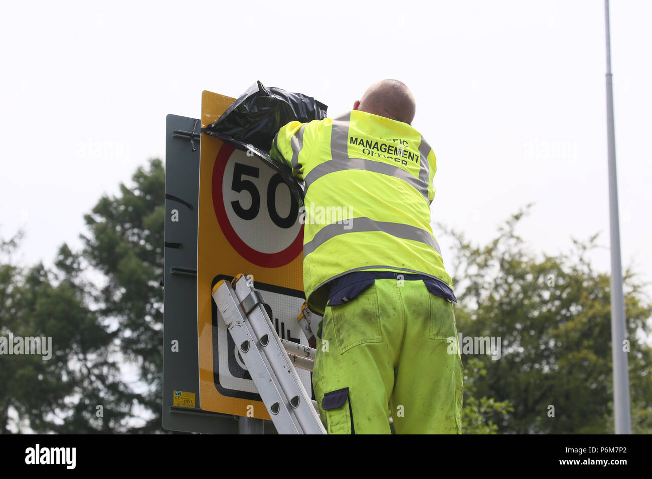 Winter Hill, Bolton, UK. 1st Jul, 2018. Bolton council worker covering a 50 speed sign on a road where fire fighters continue to battle with a blaze on Moorland above Bolton, 1st July, 2018 (C)Barbara Cook/Alamy Live News - Stock Image