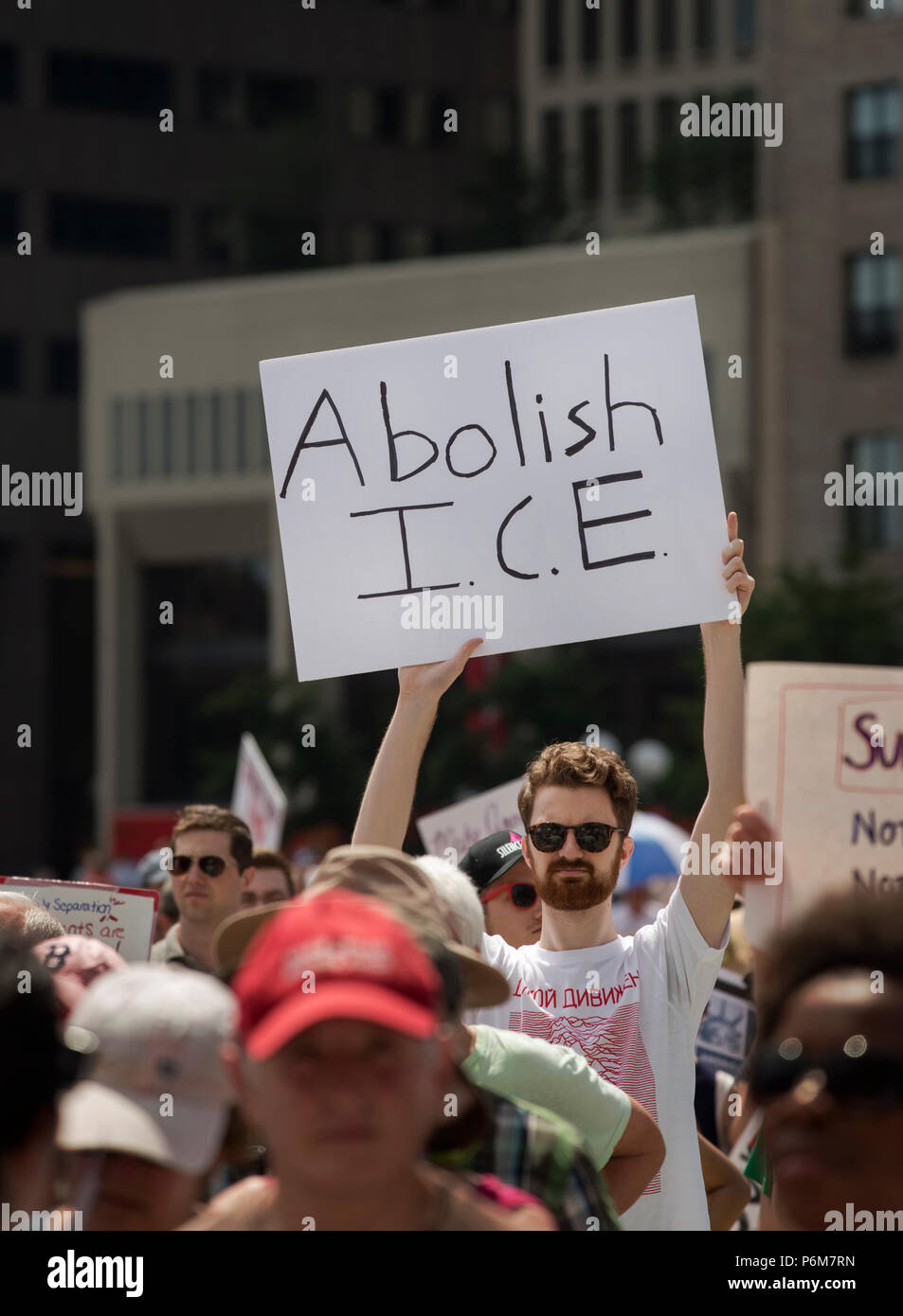 Boston, Massachusetts, USA. 30th June, 2018.  U.S. Student holding a sign 'Abolish I.C.E.' as thousands gathered in City Hall Plaza in Boston, MA, to protest the current United States administration policy of immigrant family Separation. Rallies against U.S. President Donald Trump's policy of the detention of immigrants and immigrant families separated by U.S. customs and border agents (I.C.E.) took place in more than 750 US cities on June 30th. Chuck Nacke / Alamy Live News - Stock Image