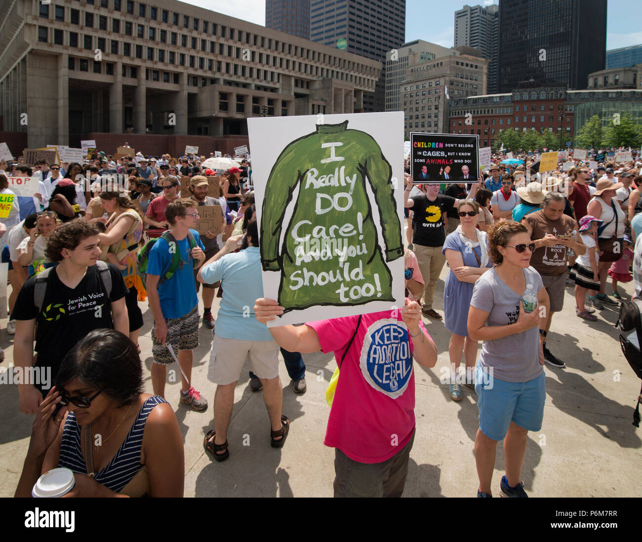 Boston, Massachusetts, USA. 30th June, 2018.  U.S. Demonstrator holding a sign mocking the Jacket that First Lady, Melania Trump wore before visiting a Texas detention shelter. Thousands Gathered in City Hall Plaza in Boston, MA during the Rally against Family Separation by the current United States administration. Rallies against U.S. President Donald Trump's policy of the detention of immigrants and immigrant families separated by U.S. customs and border agents (I.C.E.) took place in more than 750 US cities on June 30th. Credit: Chuck Nacke/Alamy Live News - Stock Image