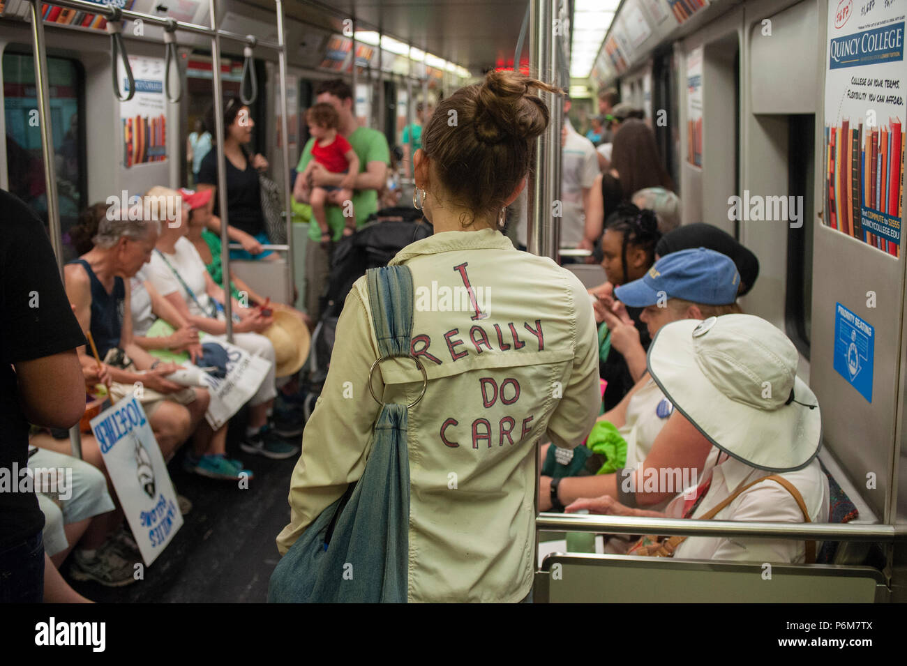 Boston, Massachusetts, USA. 30th June, 2018.  U.S. University Student wearing a coat mocking the Jacket that First Lady, Melania Trump wore before visiting a Texas detention shelter. The student and demonstrators are riding home on the Boston Metro after thousands gathered in central Boston, MA, during the Rally against Family Separation by the current United States administration. Rallies against U.S. President Donald Trump's policy of the detention immigrants and immigrant families separated by ICE took place in more than 750 US cities on June 30th.  Credit: Chuck Nacke/Alamy Live News Stock Photo
