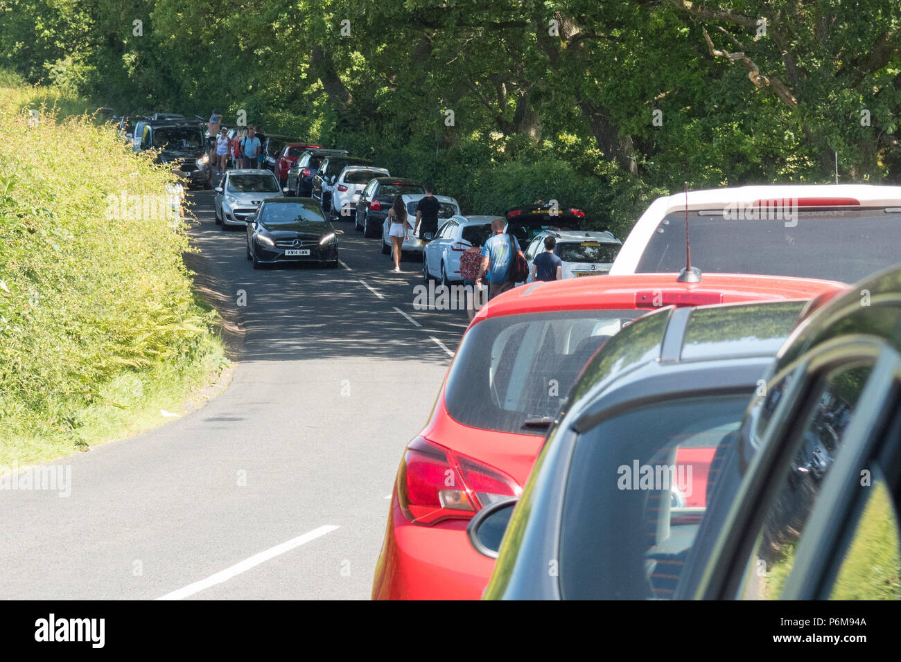 Finnich Glen, Killearn, Stirlingshire, Scotland, UK - 1 July 2018:  parking chaos and tourists walking along the B834 road in Stirlingshire visiting the increasingly popular Finnich Glen.  The B834 was closed shortly afterwards due to dangerously parked cars on both sides of the road restricting flow.  The 100 foot deep gorge between Killearn and Drymen has grown in popularity since appearing in Outlander leading to parking pressures and litter problems Credit: Kay Roxby/Alamy Live News Stock Photo