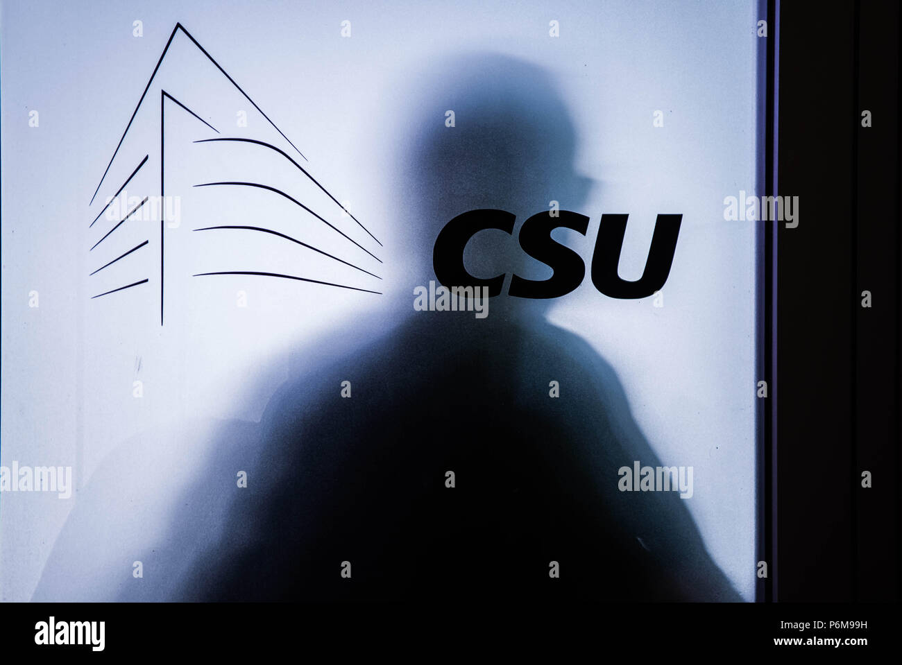 Munich, Bavaria, Germany. 1st July, 2018. Someone stands behind the frosted door of a CSU conference room where meetings are taking place to determine the future of Germany's government. Officials of the Bavarian CSU party hold a meeting to determine if the CSU will split from its union with Angela Merkel's CDU, effectively dissolving Germany's government, or if it will continue. The point of difference is regarding the sending of migrants back to the country of their first registration at the German border. Credit: Sachelle Babbar/ZUMA Wire/Alamy Live News - Stock Image