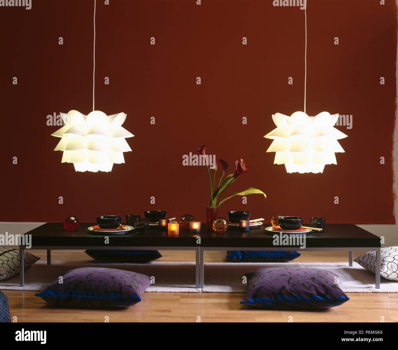 White Folded Plastic Ceiling Lights Above Grey Floor Cushions And Low Table Set For A Chinese Meal In Modern Dining Room Stock Photo Alamy