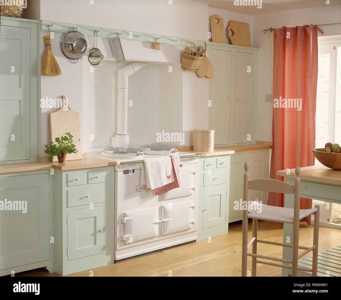 White Aga In Shaker Style Kitchen With Pale Blue Units And Peach Pink  Curtains
