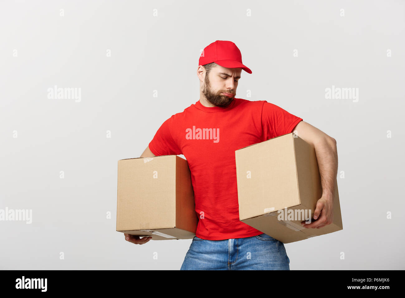 Delivery young man in red uniform holding two empty cardboard boxes isolated on white background. Copy space for advertisement - Stock Image
