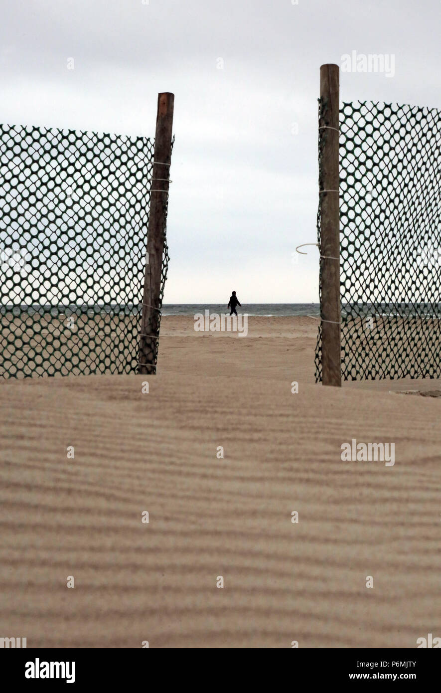 Warnemuende, woman runs in bad weather along the beach - Stock Image