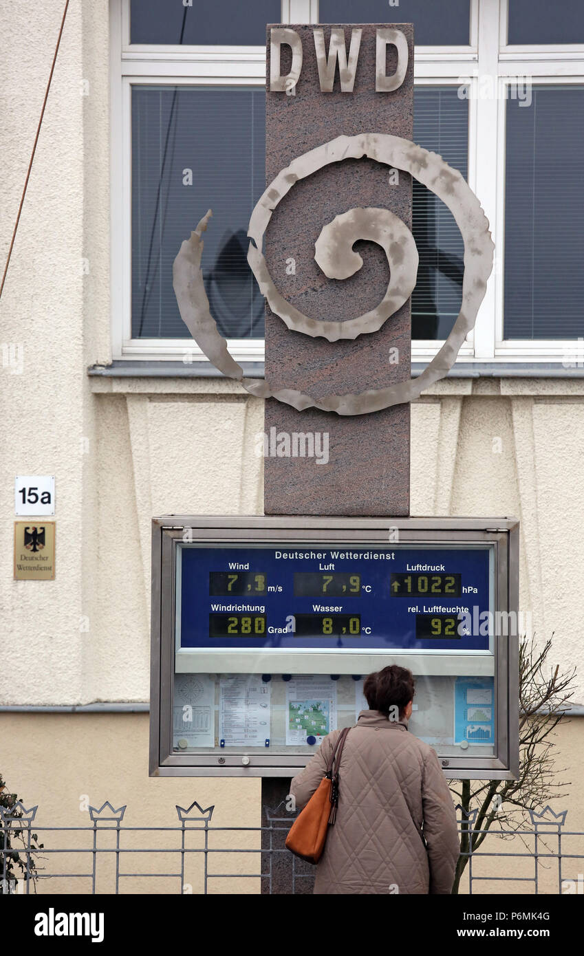 Warnemuende, woman informs herself on a scoreboard of the German Weather Service - Stock Image