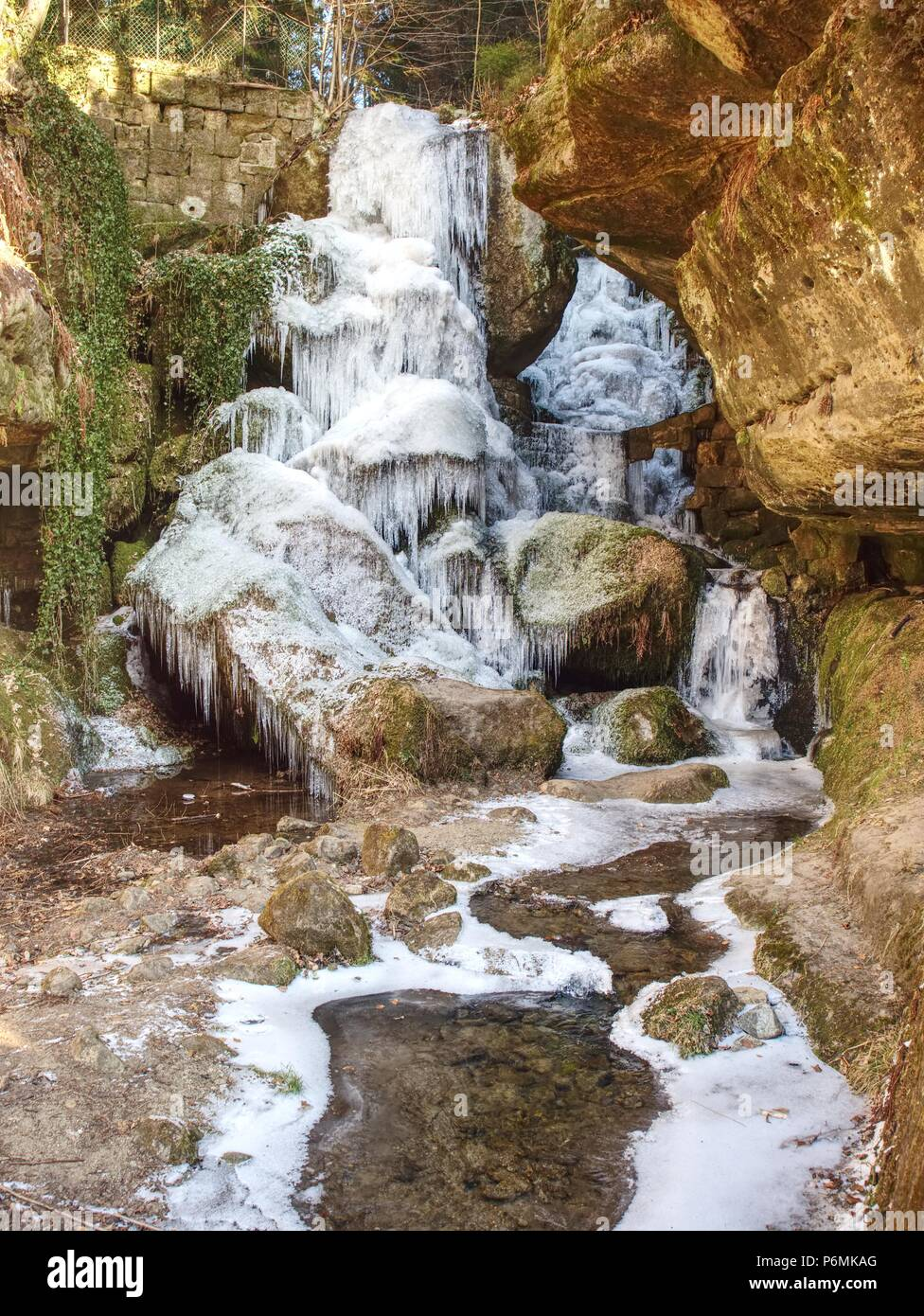 Frozen waterfall between rocks. Fallen icicle bellow waterfall, stony and mossy stream bank. - Stock Image