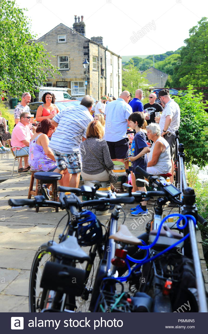 A group of people enjoying an evening pint in the Yorkshire Town of Marsden, Summer July 2018 - Stock Image