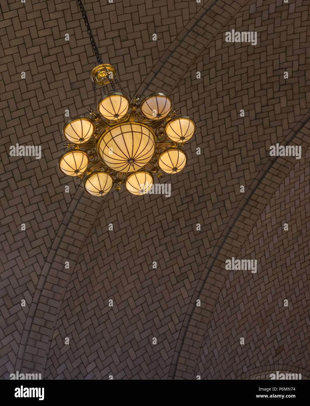 Beautifull ornate lamp hangs from a herrinbone styled acrhed ceiling in the reception area on Ellis Island, off Manhattan, New York City ornate lamp h - Stock Image