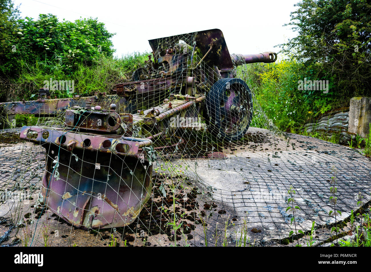 A German F18 150mm howitzer sits in its fortified emplacement under camouflage netting at the Maisey Battery, Normandy - Stock Image