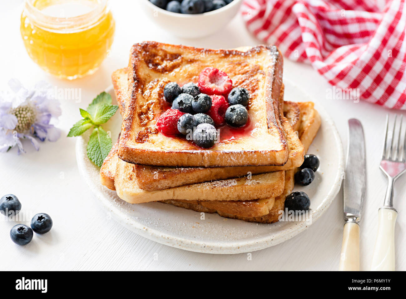Delicious French toast with berries and honey on white plate. Tasty breakfast concept - Stock Image