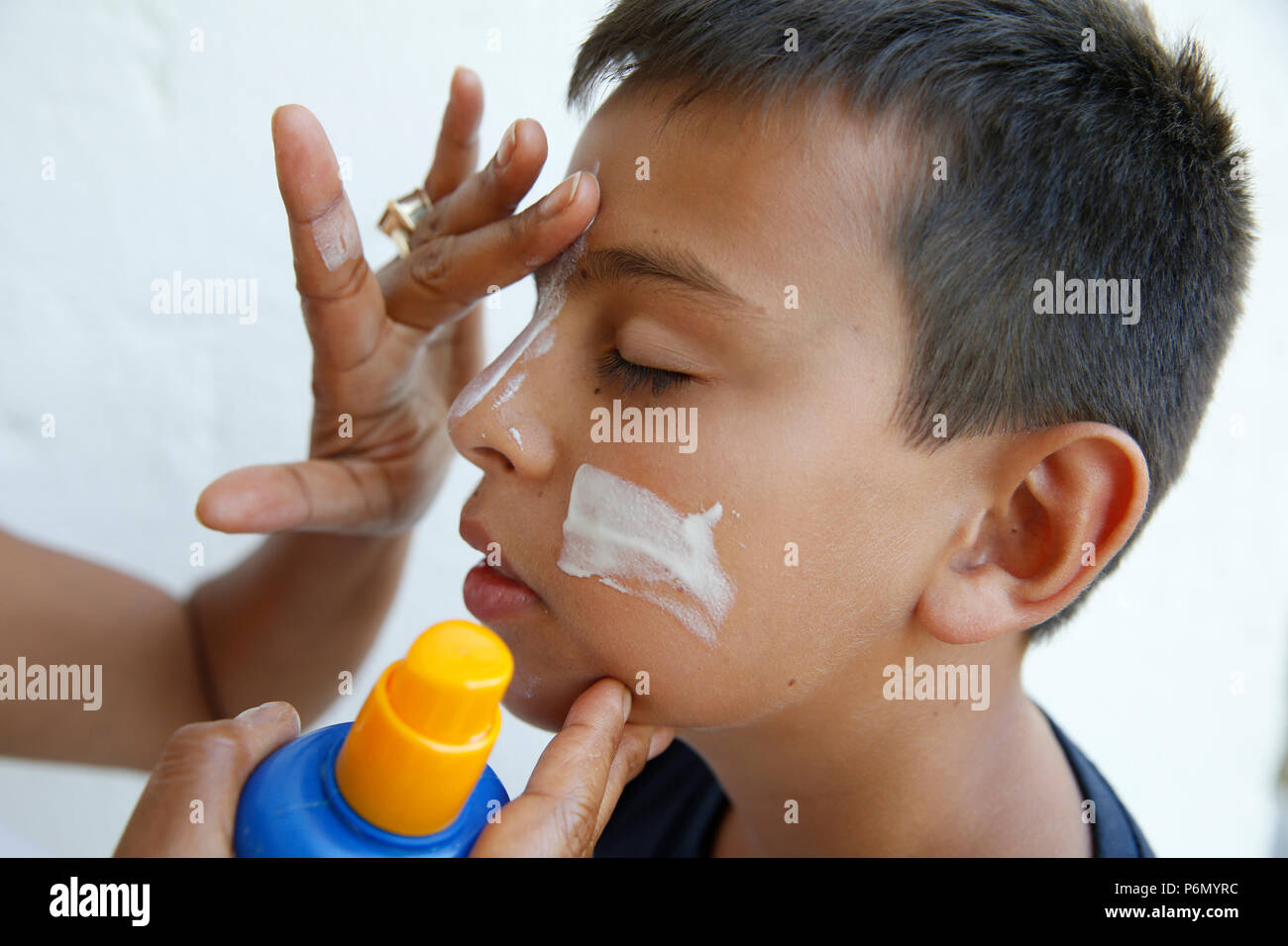 Mother putting sun protection cream on her son's face in Salento, Italy. - Stock Image
