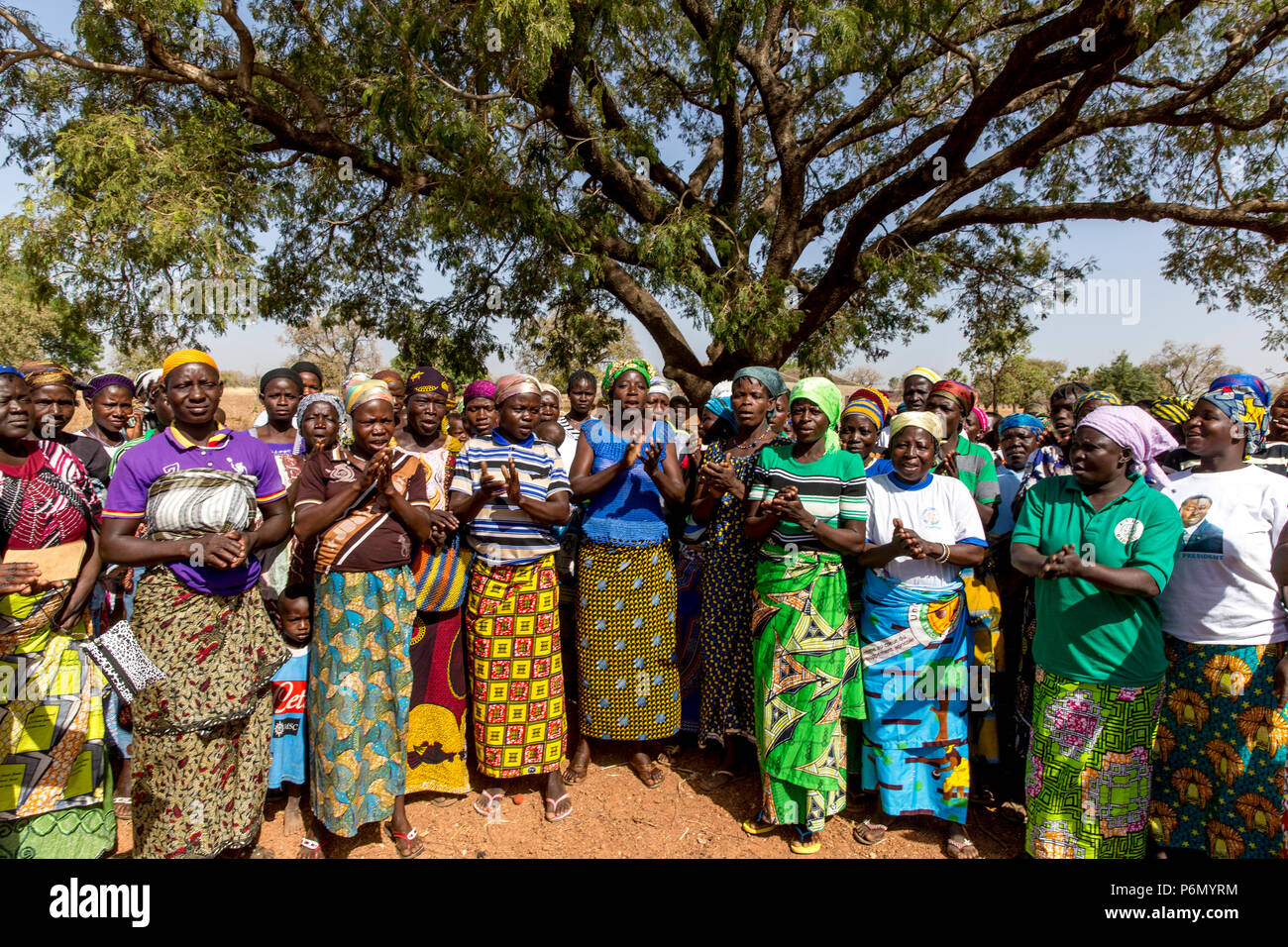 Members of a women's microfinance cooperative welcoming a visitor in Northern Togo. - Stock Image