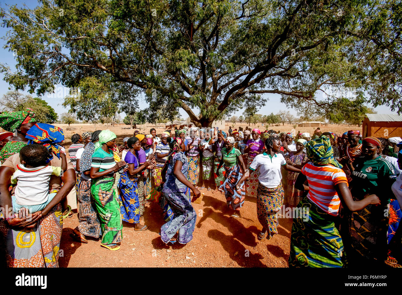Members of a women's microfinance cooperative welcoming a visitor with dances in Northern Togo. - Stock Image