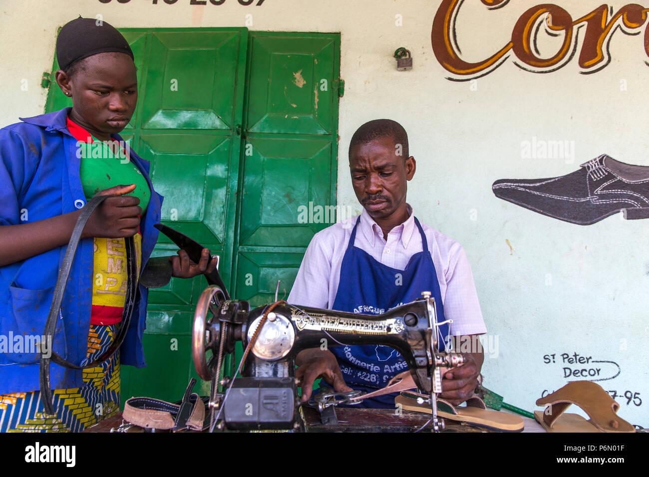 Dapaong apprentice and cobbler whose business is financed by microfinance. Togo. - Stock Image