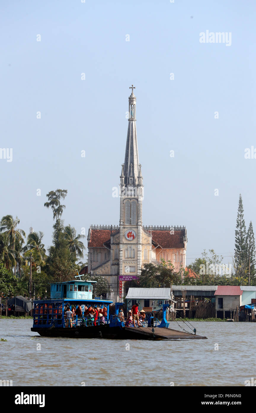 Ferry Boat  with view of Catholic Cathedral. Cai Be. Vietnam. Stock Photo