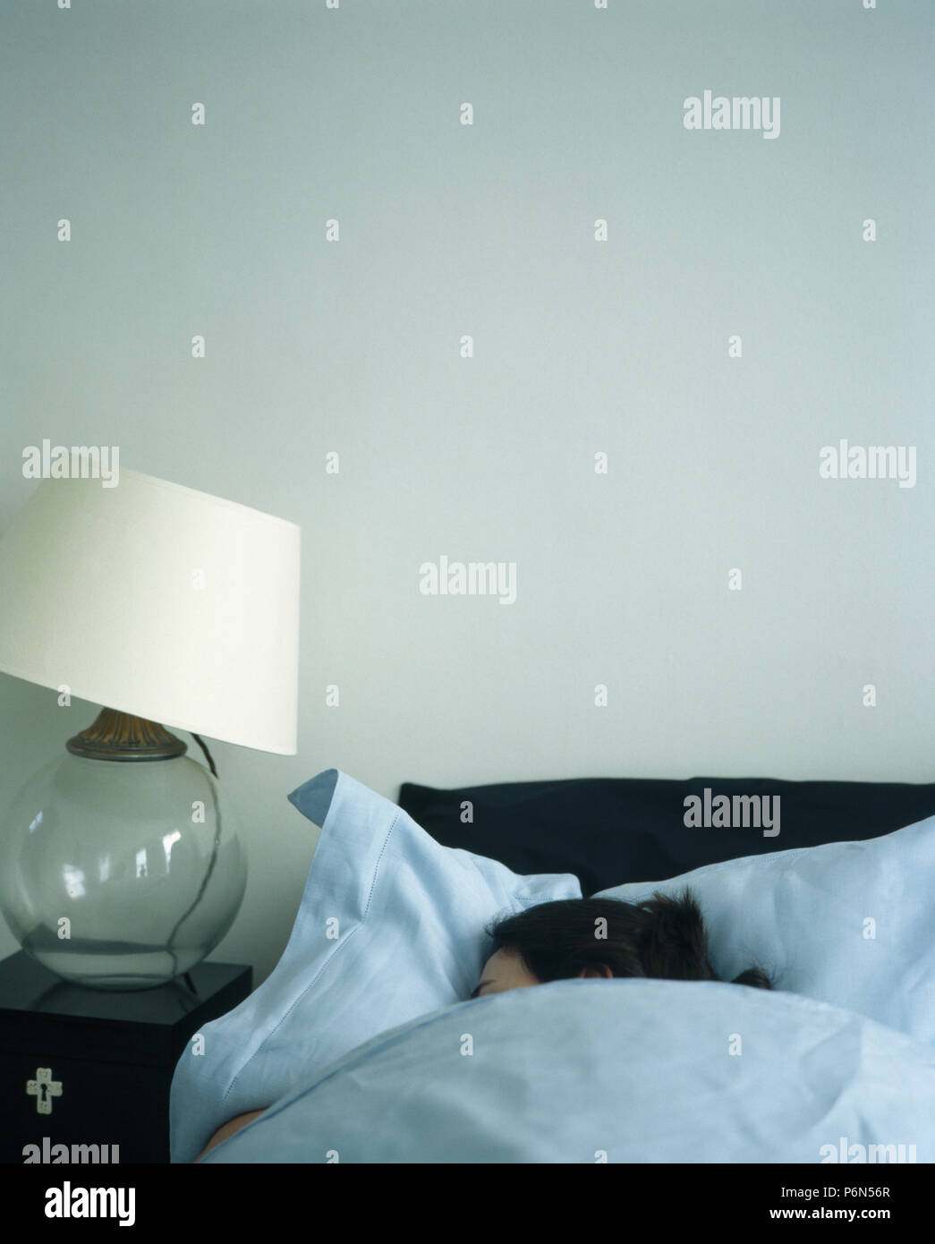 Sleeping female in comfy bed - Stock Image
