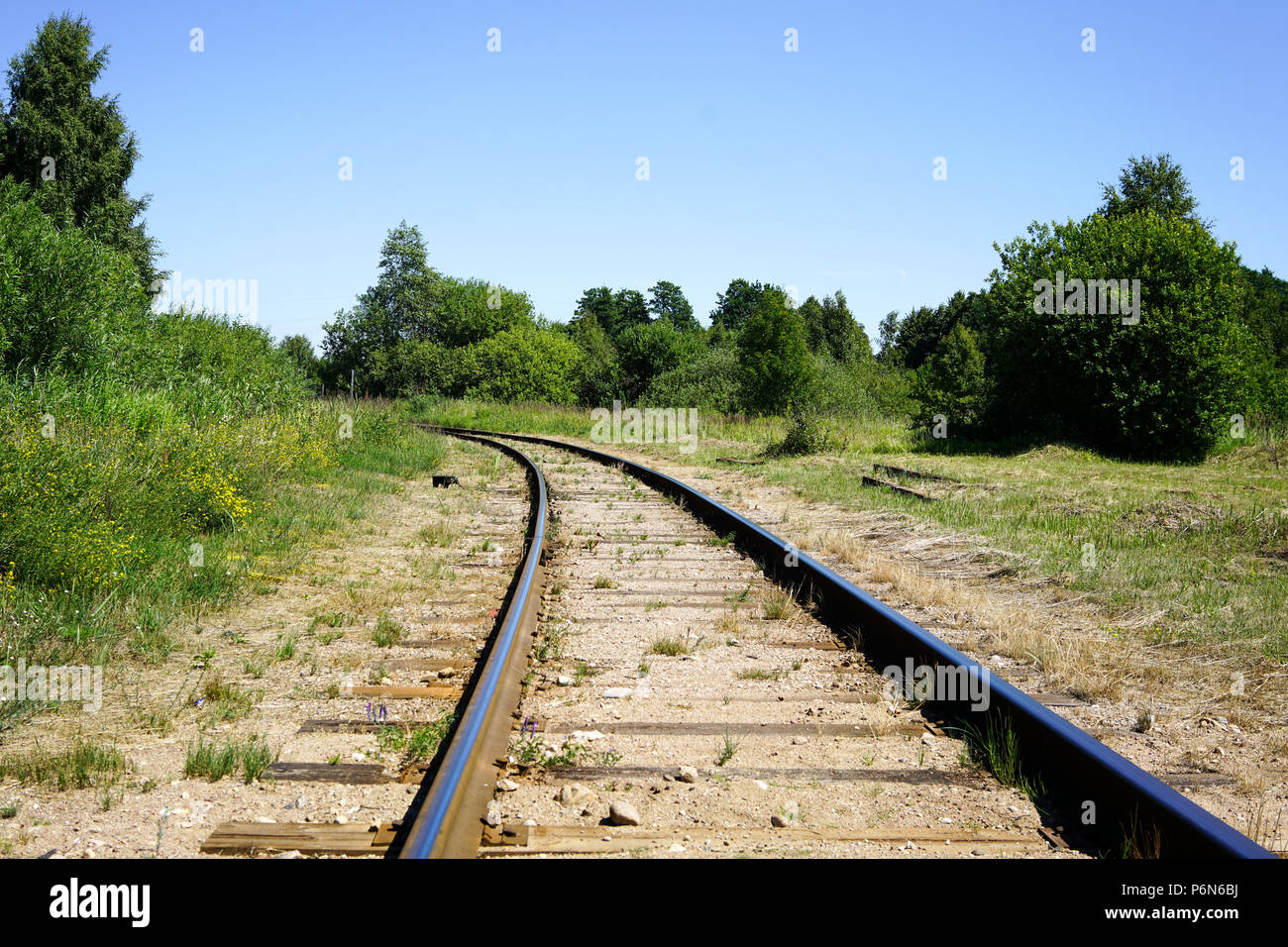 Curving rail line winds its way through trees and forests. - Stock Image