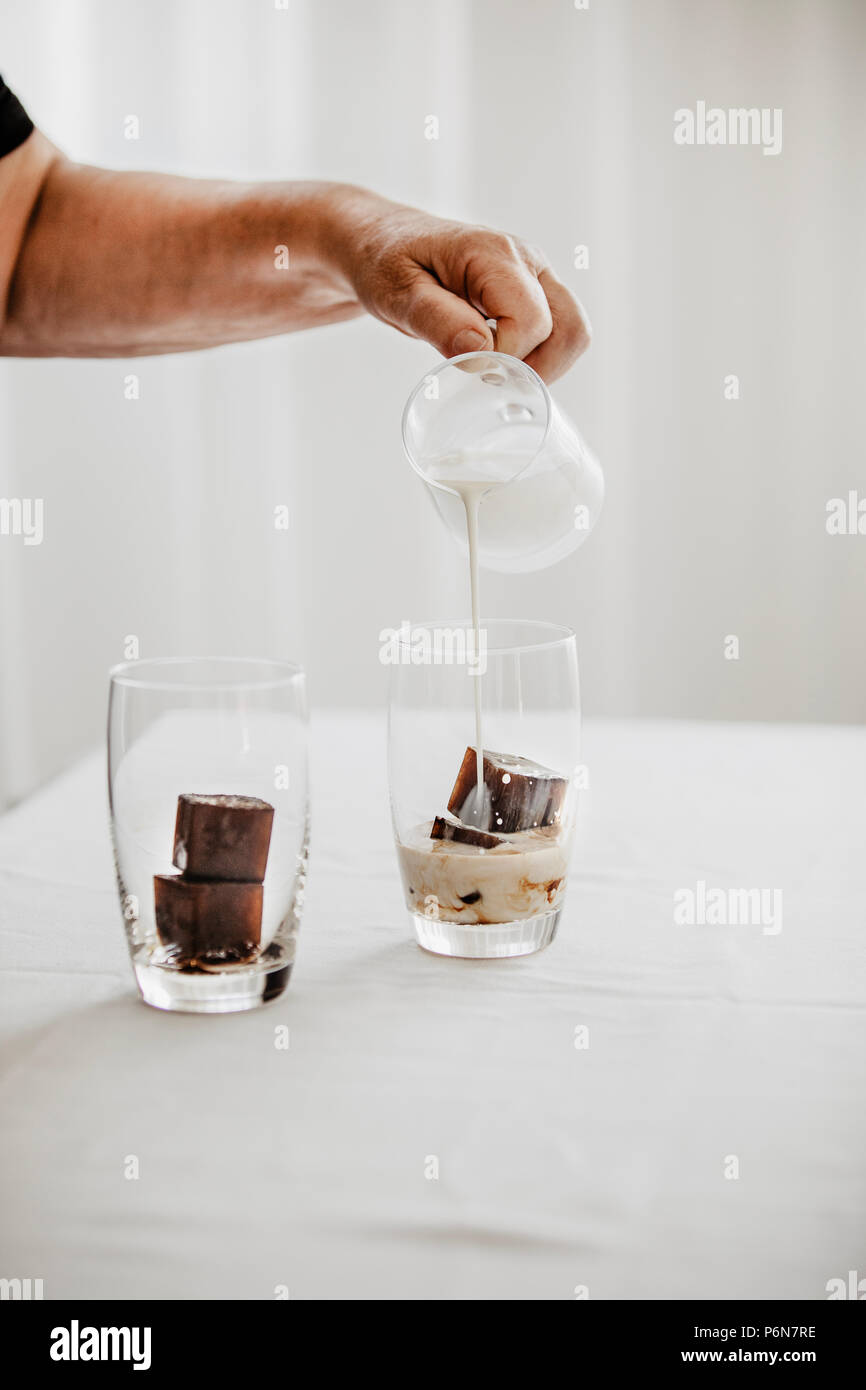 Woman preparing iced coffee. Frozen coffee ice cubes in a glass poured with milk to make a refreshing summer drink. White background. Body parts. - Stock Image