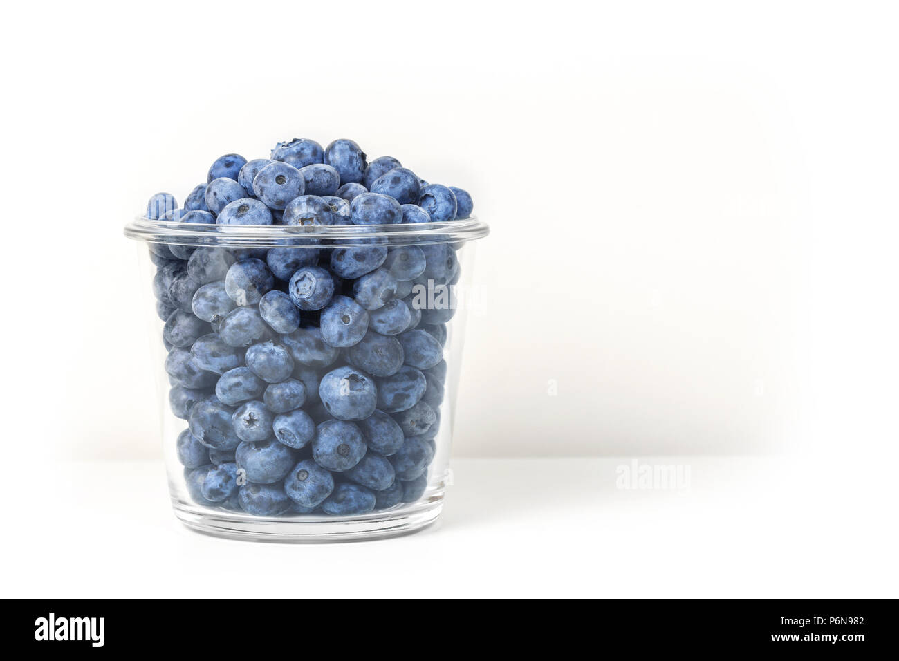 Fresh organic blueberries in transparent glass bowl isolated on white background. Sweet tasty bilberries in pot. Summer seasonal natural vitamines and antioxidants. Healthy diet and nutrition concept Stock Photo